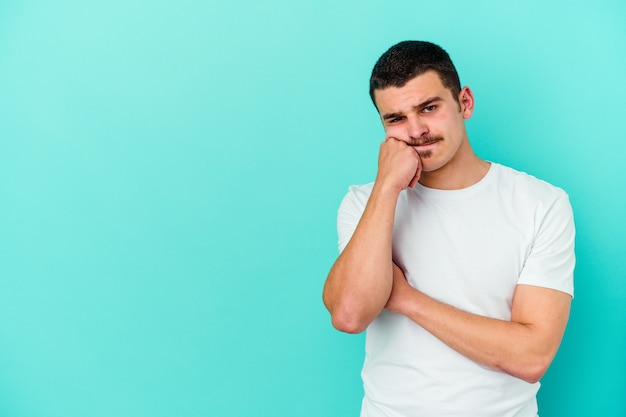 Молодой кавказский человек, изолированные на синем фоне, который чувствует себя грустным и задумчивым, глядя на пространство для копирования.