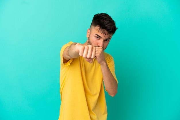 Молодой кавказский человек изолирован на синем фоне с боевым жестом