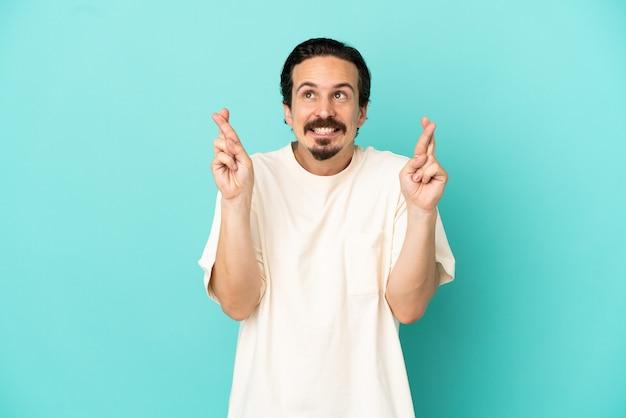 Молодой кавказский человек изолирован на синем фоне со скрещенными пальцами и желает лучшего