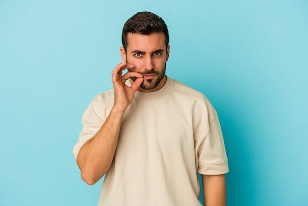 秘密を保持している唇に指で青い背景に分離された若い白人男性。