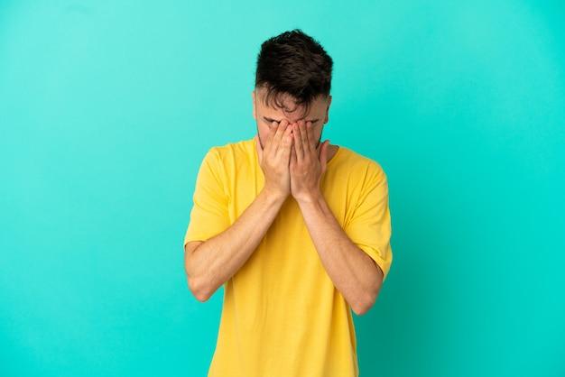Молодой кавказский человек изолирован на синем фоне с усталым и больным выражением лица