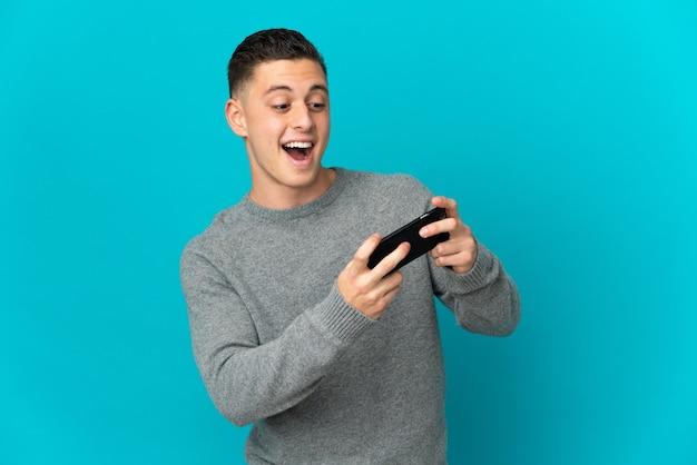 Молодой кавказский человек изолирован на синем, играя с мобильным телефоном