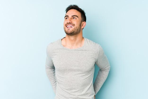 Молодой кавказский человек изолирован на синем расслабленном и счастливом смехе, вытянув шею, показывая зубы.