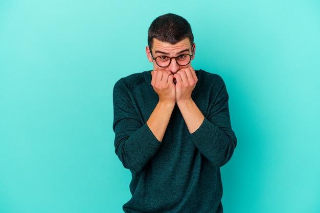 Молодой кавказский человек изолирован на синей стене, кусая ногти, нервный и очень взволнованный.