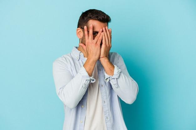 青い壁に孤立した若い白人男性が指で瞬き、恥ずかしい顔を覆っている。