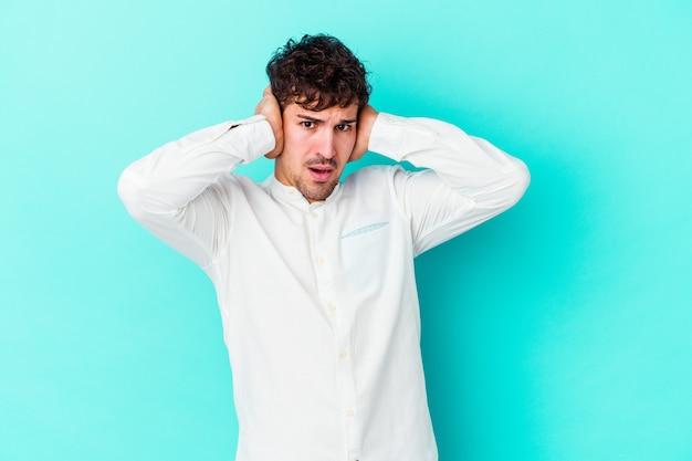 너무 시끄러운 소리를 듣지 않으려 고 손으로 귀를 덮고 파란색 벽에 고립 된 젊은 백인 남자.