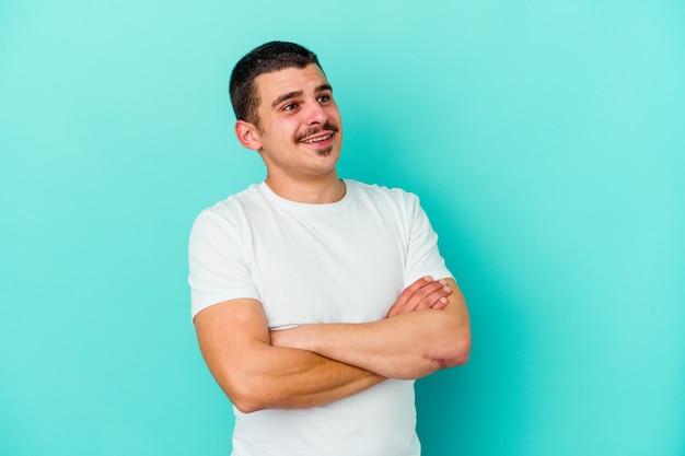 목표와 목적 달성을 꿈꾸는 파란색 벽에 고립 된 젊은 백인 남자