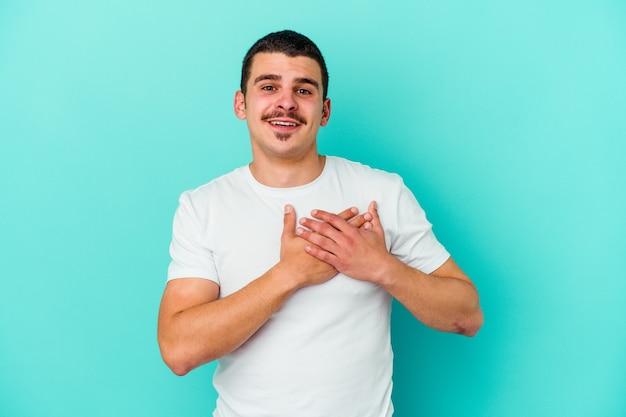 파란색 벽에 고립 된 젊은 백인 남자는 가슴에 손바닥을 눌러 친절한 표현을 가지고