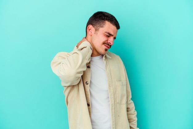 Молодой кавказский мужчина изолирован на синей стене с болью в шее из-за стресса, массируя и трогая ее рукой