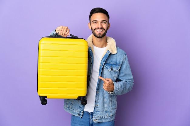 Молодой кавказский мужчина изолирован на синей стене в отпуске с чемоданом