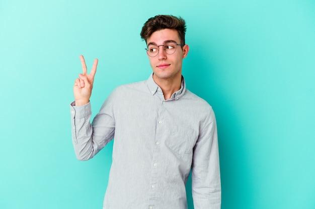 青い壁に孤立した若い白人男性は、指で平和のシンボルを示して楽しくてのんきです。