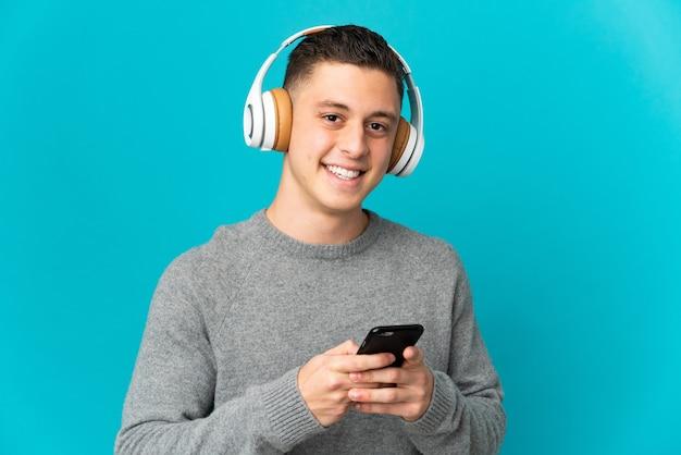 Молодой кавказский человек изолирован на синей стене, слушает музыку с помощью мобильного телефона и смотрит вперед