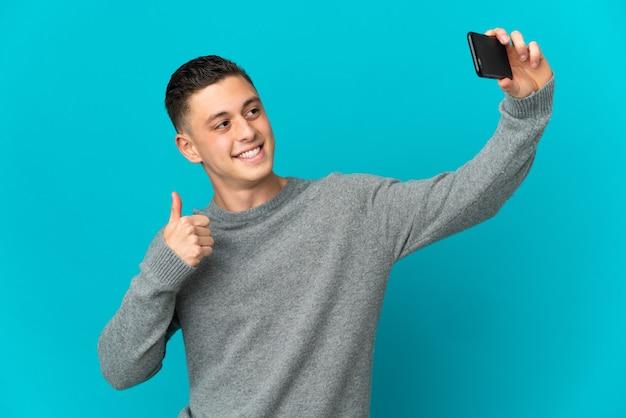 Молодой кавказский человек изолирован на синей стене, делая селфи с мобильным телефоном