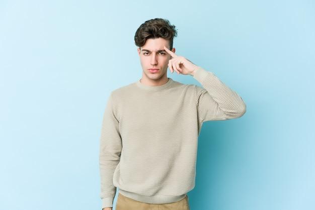 Молодой кавказский человек изолирован на синей стене указывая висок пальцем, думая, сосредоточился на задаче.