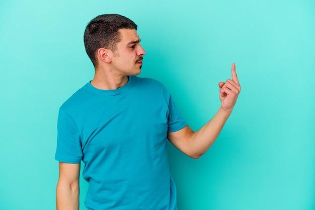 誘うようにあなたに指で指している青い壁に孤立した若い白人男性が近づく
