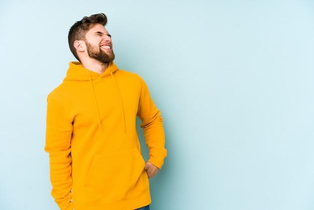 Молодой кавказский человек, изолированные на синей стене, расслабленный и счастливый смех, вытянув шею, показывая зубы.