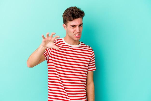 青い壁に孤立した若い白人男性は、猫を模倣した爪、攻撃的なジェスチャーを示しています。
