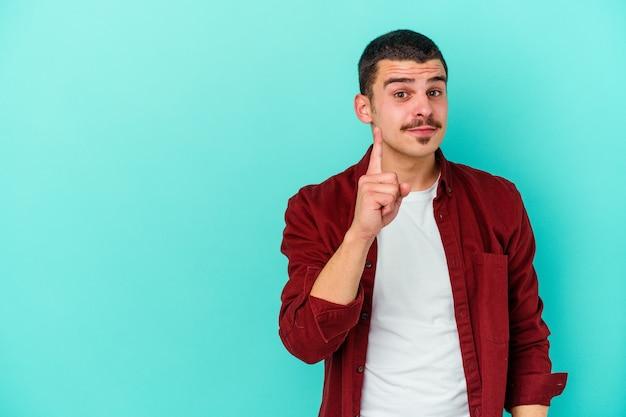 손가락으로 번호 하나를 보여주는 파란색 벽에 고립 된 젊은 백인 남자.
