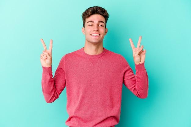 勝利のサインを示し、広く笑顔で青い壁に孤立した若い白人男性。
