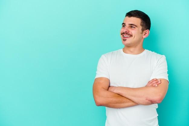 腕を組んで自信を持って笑って青い壁に孤立した若い白人男性