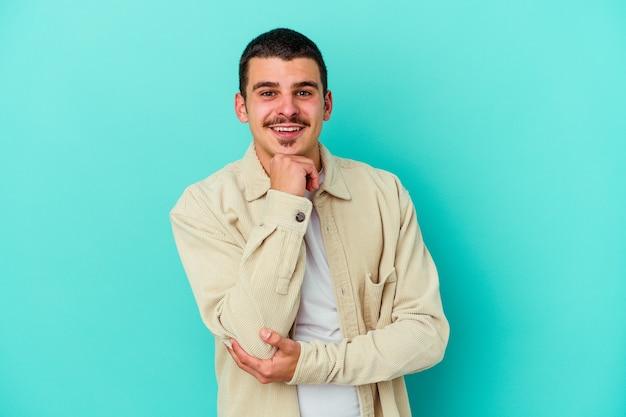 幸せで自信を持って笑顔、手で顎に触れる青い壁に孤立した若い白人男性