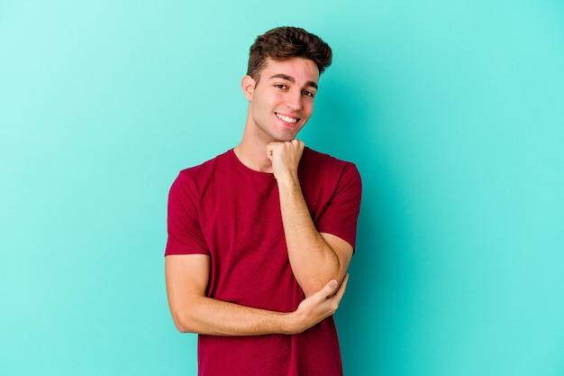 행복 하 고 자신감, 손으로 턱을 만지고 웃 고 파란색 벽에 고립 된 젊은 백인 남자.