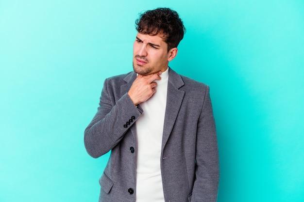 Молодой кавказец, изолированный на синей стене, страдает от боли в горле из-за вируса или инфекции.