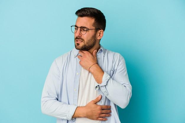 파란색 벽에 고립 된 젊은 백인 남자는 바이러스 또는 감염으로 인해 목에 통증을 앓고 있습니다.