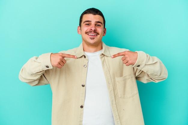 青い壁に孤立した若い白人男性は、指で指して驚いて、広く笑っています。 Premium写真