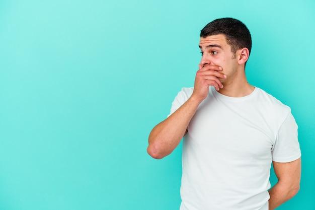 手で口を覆うコピースペースを思慮深く見て青い壁に孤立した若い白人男性