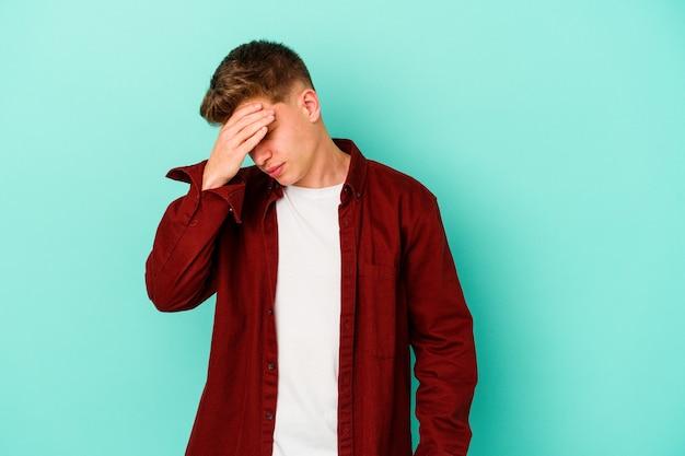 Молодой кавказский мужчина изолирован на синей стене, касаясь висков и испытывая головную боль
