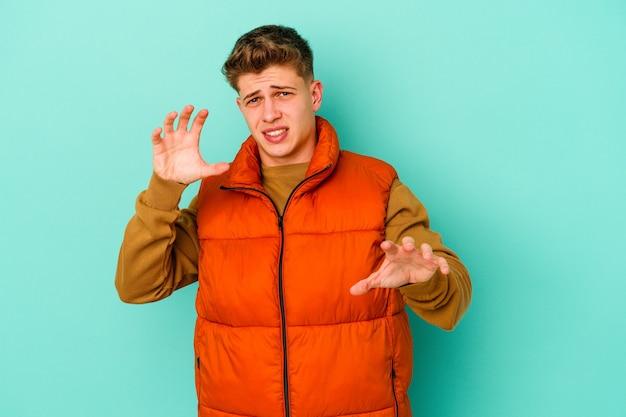 青い壁に孤立した若い白人男性が緊張した手で叫んで動揺
