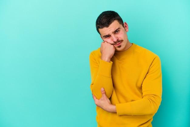 Молодой кавказский мужчина изолирован на синей стене, который чувствует себя грустным и задумчивым, глядя на копировальное пространство