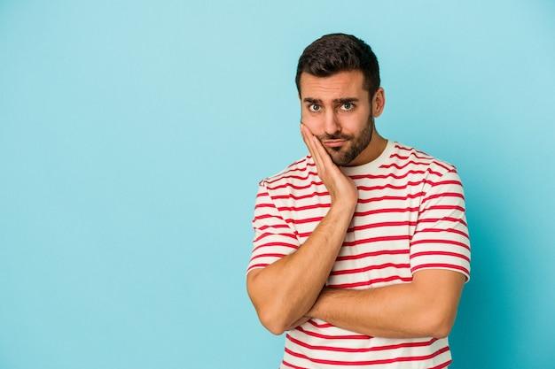Молодой кавказский человек изолирован на синей стене, который чувствует себя грустным и задумчивым, глядя на пространство для копирования.