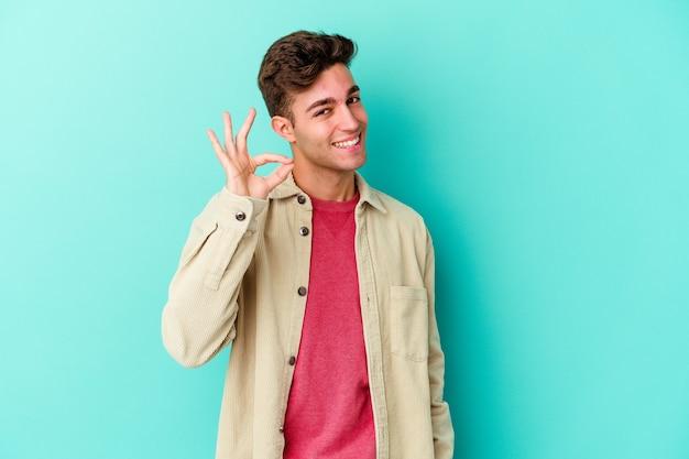 青い壁に隔離された若い白人男性は目をまばたきし、手で大丈夫なジェスチャーを保持します。