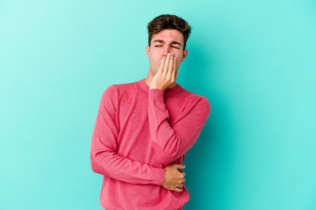 手で口を覆う疲れたジェスチャーを示すあくびをする青い壁に孤立した若い白人男性