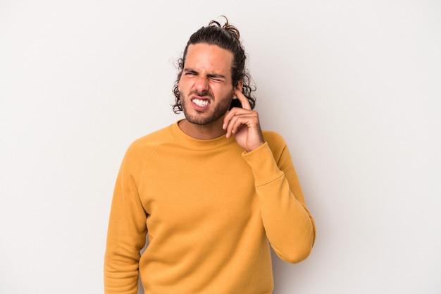 灰色の背景に孤立した若い白人男性が、耳を指で覆い、大声で周囲の環境にストレスを感じ、必死になっています。