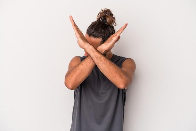 灰色の背景に孤立した若い白人男性は、2つの腕を交差させたまま、概念を否定します。