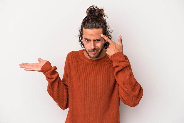 人差し指で失望のジェスチャーを示す灰色の背景に分離された若い白人男性。