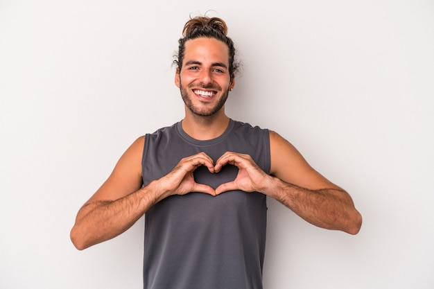 笑顔と手でハートの形を示す灰色の背景に分離された若い白人男性。