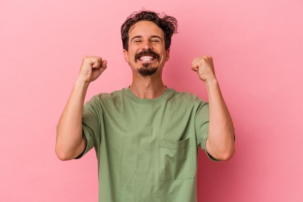 勝利、情熱と熱意、幸せな表現を祝うピンクの背景に孤立した若い白人男性。
