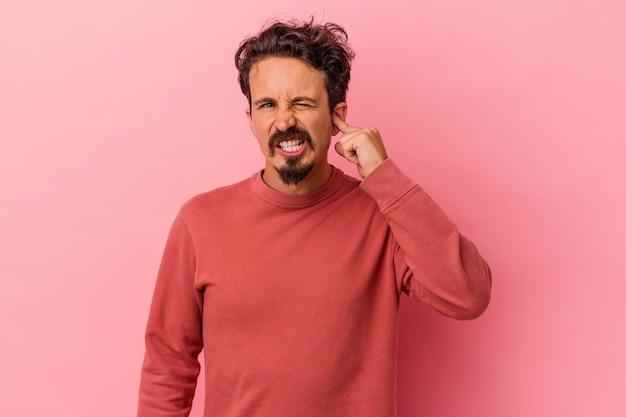 指で耳を覆っているピンクの背景に孤立した若い白人男性は、大声で周囲にストレスを感じ、必死になっています。