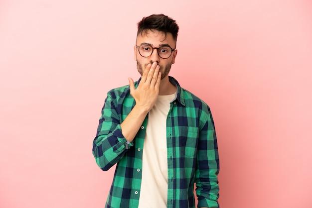 Молодой кавказский мужчина изолирован на розовом фоне, прикрывая рот рукой