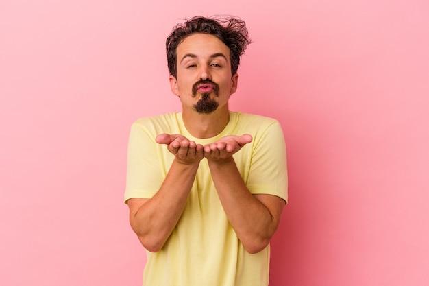 ピンクの背景に孤立した若い白人男性は、唇を折り、手のひらを持って空気のキスを送信します。