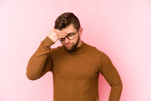 顔の正面に触れて、頭痛を持っているピンクの背景に分離された若い白人男性。