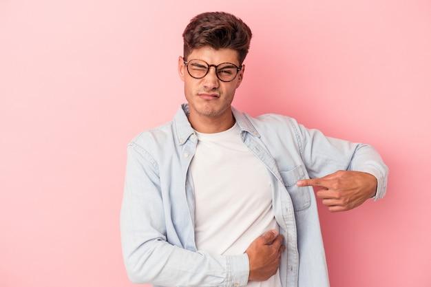 肝臓の痛み、胃の痛みを持っているピンクの背景に分離された若い白人男性。