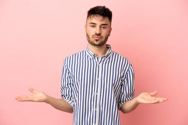 疑いを持ってピンクの背景に分離された若い白人男性