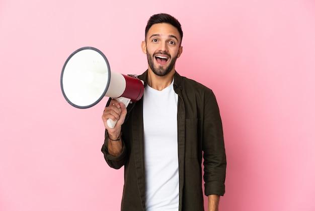 Молодой кавказский человек изолирован на розовом фоне, держа мегафон и с удивленным выражением лица