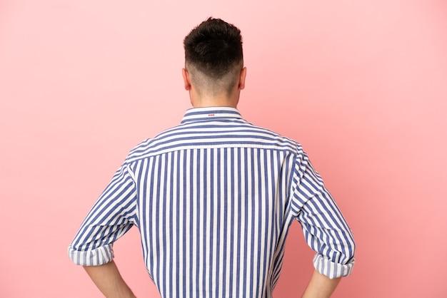 Молодой человек кавказской изолирован на розовом фоне в задней позиции