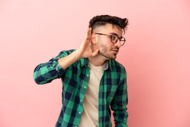 Молодой кавказский человек изолирован на розовом фоне, слушая что-то, положив руку на ухо
